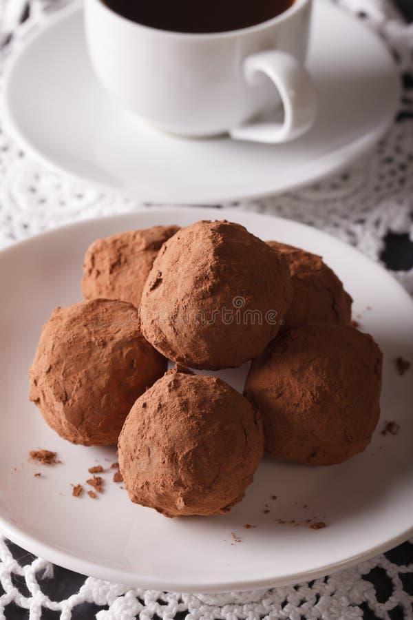 Chokladtryfflar närbild och kaffe på tabellen vertikalt arkivbild