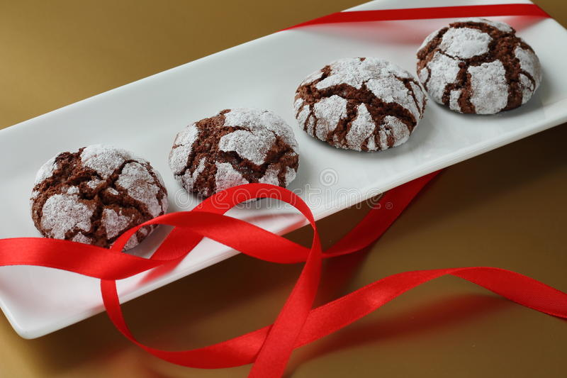 Chokolate crinkles cookies. On a white plate with heart-shaped ribbon royalty free stock image