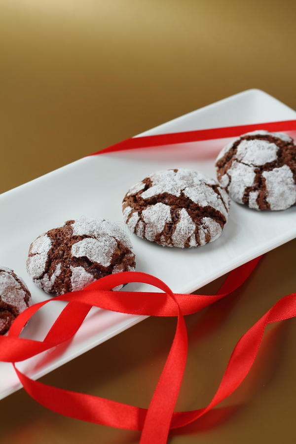 Chokolate crinkles cookies. On a white plate with heart-shaped ribbon stock photo