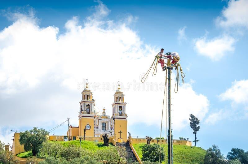 Cholula, Мексика - 31-ое октября 2018 Лос Voladores - люди летания и церковь исторического города San Pedro Cholula стоковое изображение rf