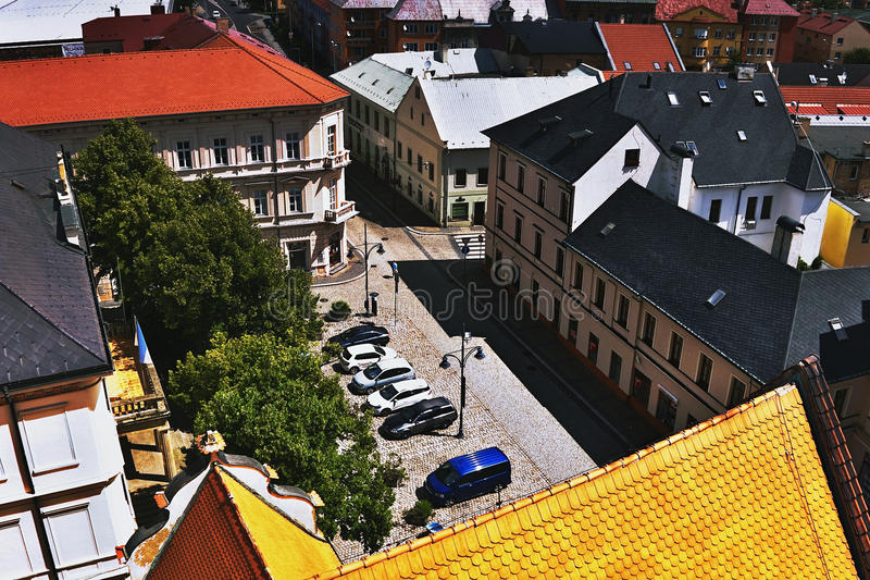 2016/06/18 Chomutov city, Czech republic - cobbled square 'Husovo namesti'. With a small parking area and large deciduous trees before the start of the summer stock images
