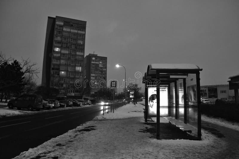 Chomutov, república checa - 20 de janeiro de 2017: rua de Bezrucova da noite com estação de ônibus no primeiro plano durante a si fotografia de stock
