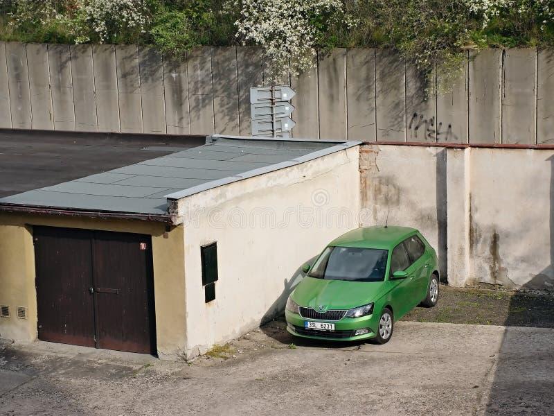 Chomutov, Tschechische Republik - 25. April 2018: neues grünes Auto Skoda Fabia von 3 Generationsstand zwischen Garagen ist Frühl lizenzfreies stockbild