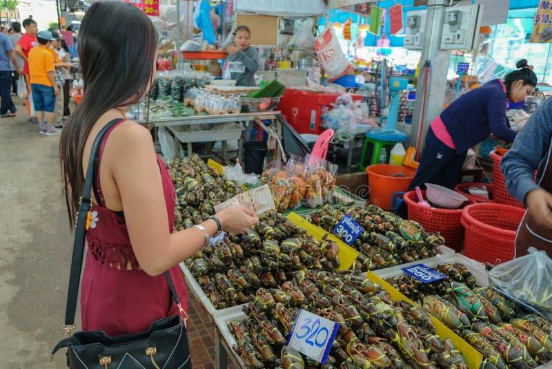 Chon Buri Province Thailand - December 13,2018: Kvinnor väljer att köpa gyttjakrabbor med försäljare på arkivfoto