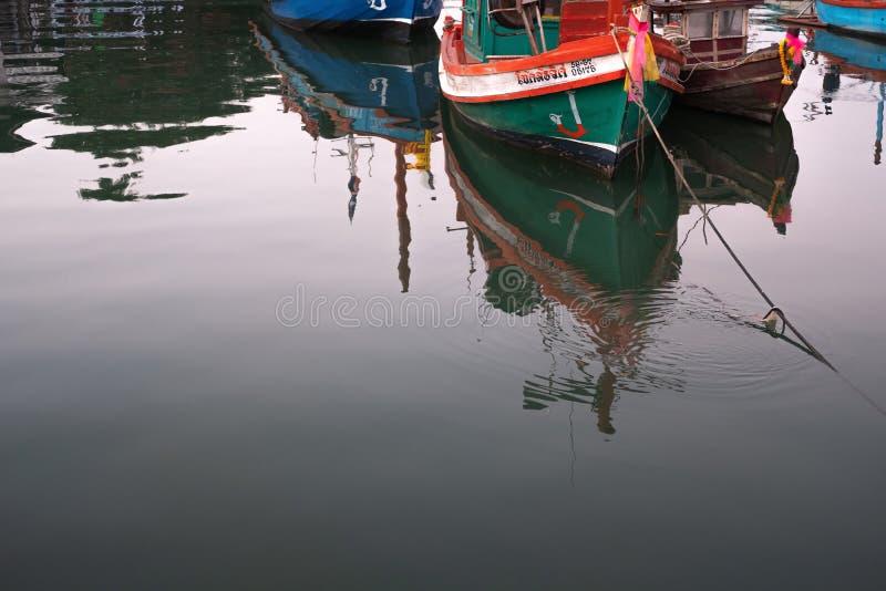 CHON BURI, TAILÂNDIA - 16 DE FEVEREIRO DE 2019: Reflexão sobre a água do barco pescador local que ancora no porto de pesca local, imagens de stock royalty free