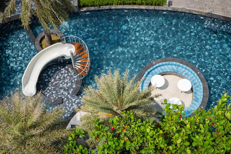 CHON BURI, THAILANDIA - 16 FEBBRAIO 2019: Vista dall'alto della piscina tropicale, dello scivolo d'acqua, dei sedili e della tavo fotografia stock libera da diritti