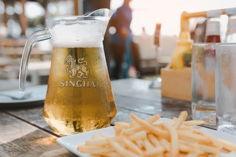 CHONBURI, TAILANDIA - 21 de abril de 2018: Una jarra de cerveza de Singha con un vidrio de cerveza en la tabla imagen de archivo libre de regalías