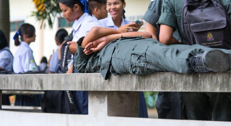 CHONBURI, THAILAND 3. AUGUST 2017: Schüler tragen die Militärstudentenuniform, die auf einer Bank liegt, die vom Zement in der Sc lizenzfreie stockfotografie