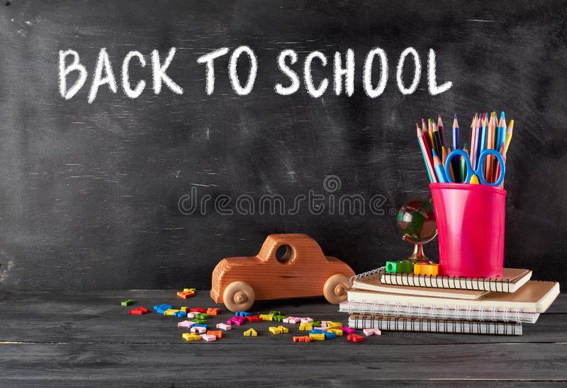 chool supplies: notebook, pencils, scissors and a wooden retro toy car royalty free stock photography