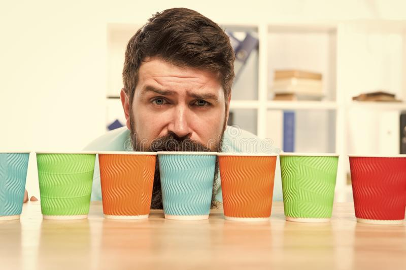 Choose from alternatives. Man bearded choosing one of lot colorful paper cups. Alternative concept. Pick one. Diversity. And recycling. Eco paper cup. Coffee to stock photos