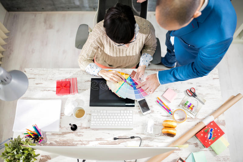 Choose appropriate colorFemale and male employer in designer ph. Two employers in designer photo studio processing stock photo