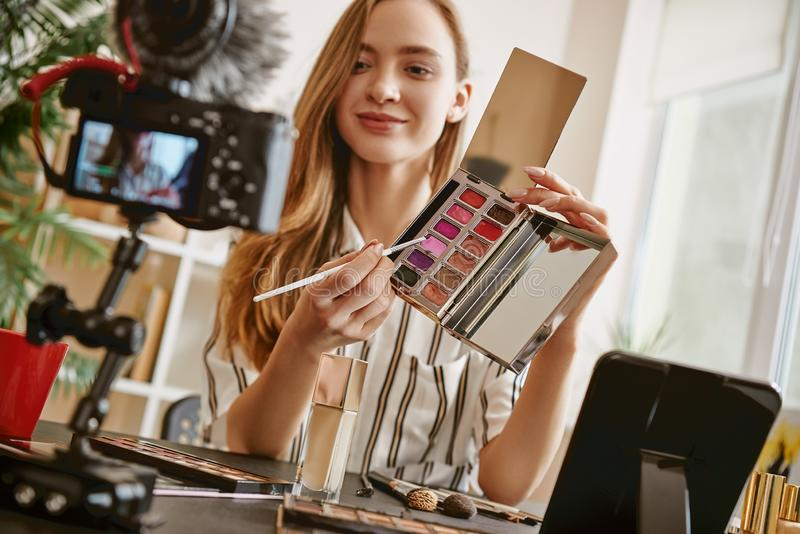 Choose it. Cute female blogger presenting a makeup palette and smiling while looking at camera stock photos