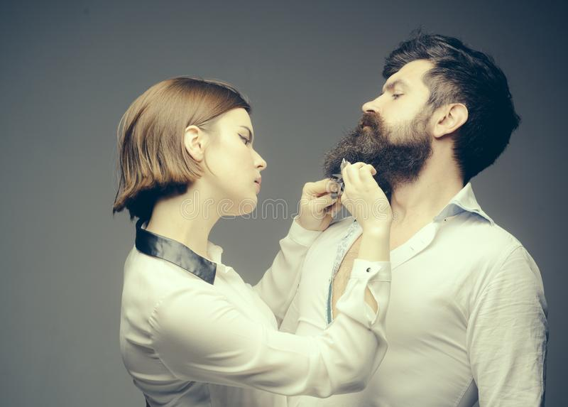 Choose final style. Match beard to your face shape. Girl barber with scissors cutting hair of brutal bearded hipster. Barber expert grooming tips. Beard care royalty free stock image