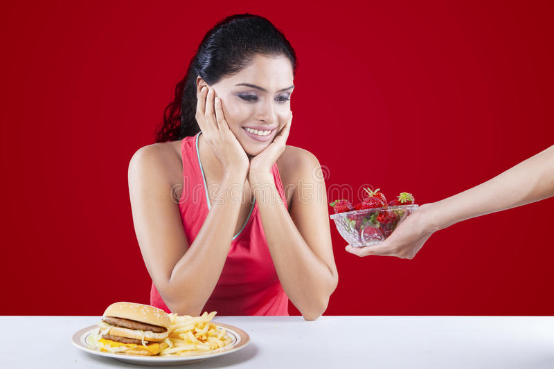 Choose Between Hamburger Versus Strawberry. Indian woman choosing a bowl of strawberry and refuse hamburger, shot with red background stock photo