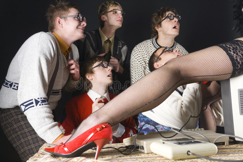 Choose me... Five nerdy guys looking at stripteaser who is sitting on monitor. They are smiling and looking fascinated. Side view royalty free stock photos