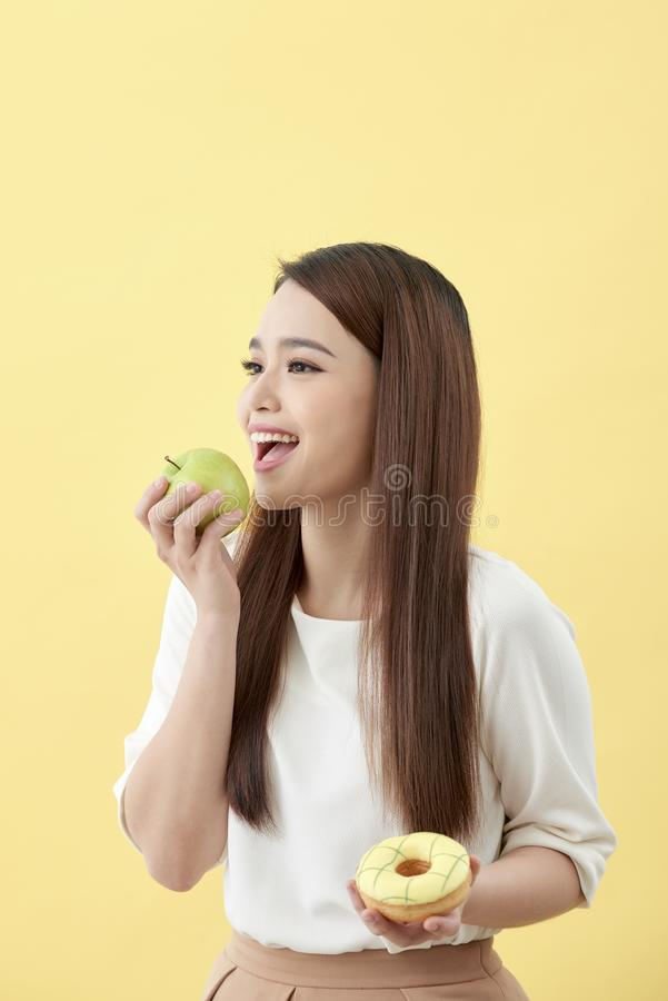 Choose a right choice for good health. Women is choosing choice between donut and green apple isolated over yellow royalty free stock photos