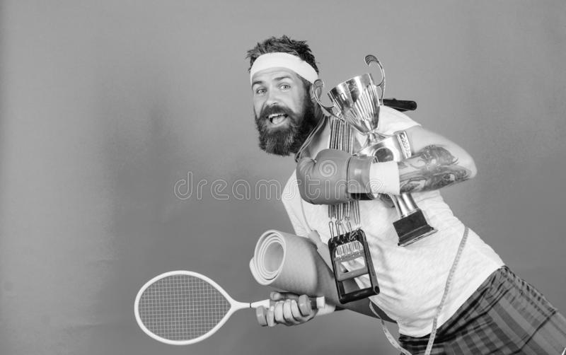 Choose sport you like. Man bearded athlete hold sport equipment jump rope fitness mat boxing glove expander racket and. Golden goblet. Sport shop assortment royalty free stock photo