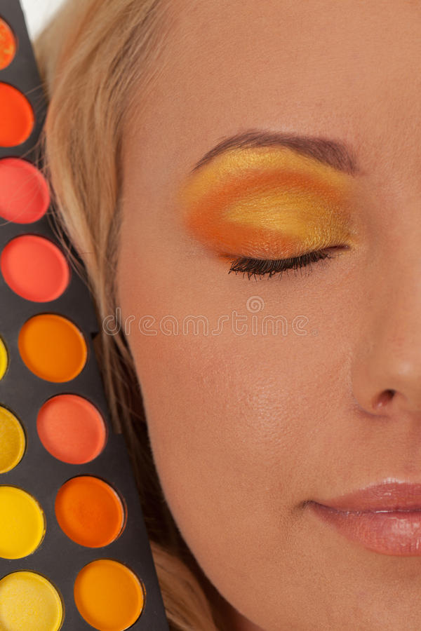 Choose your color. Young girl with orange and yellow make-up royalty free stock photos