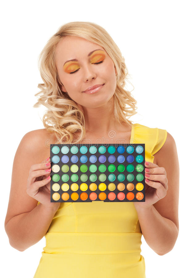 Choose your color. Smiling girl is holding shadow palette stock photography