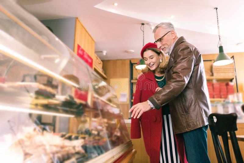 Loving stylish couple of mature man and woman choosing French desserts royalty free stock photo