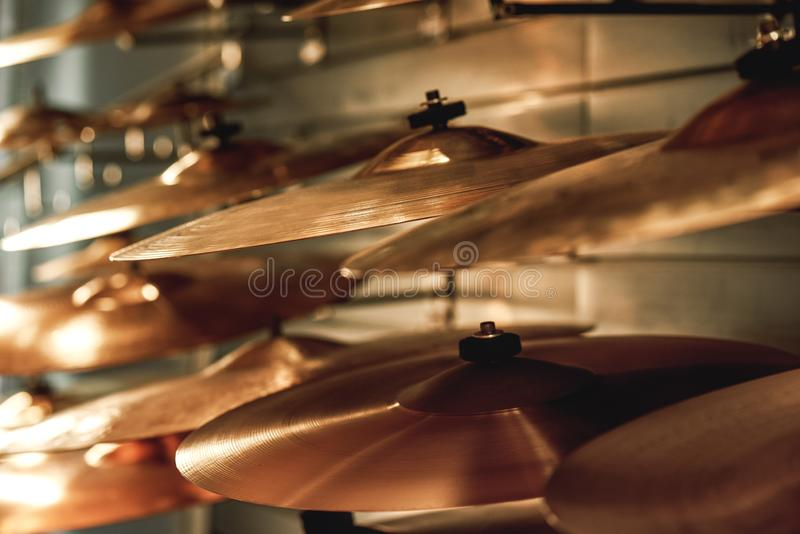Choosing drum set. Close up view of several golden drum cymbals in a music shop. Music concept stock images