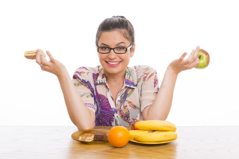 Choosing between fruits and cakes stock images