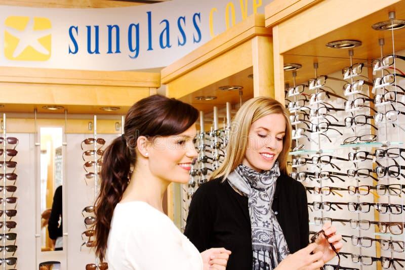 Choosing glasses. Optician assisting lady in choosing glasses stock photos