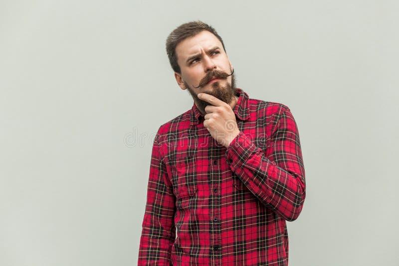 choosing Hombre de negocios de la creatividad con la barba y bigote que mira para arriba y que piensa imágenes de archivo libres de regalías