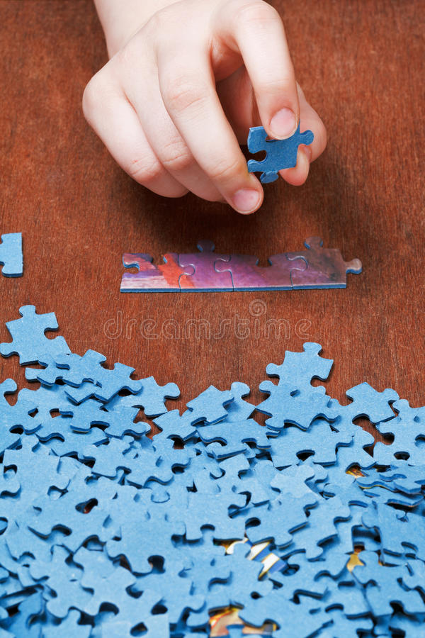 Choosing of jigsaw puzzles. On wooden table royalty free stock images