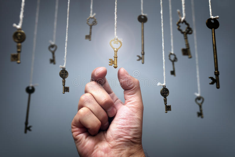 Choosing the key to success. From hanging keys concept for aspirations, achievement and incentive stock photography