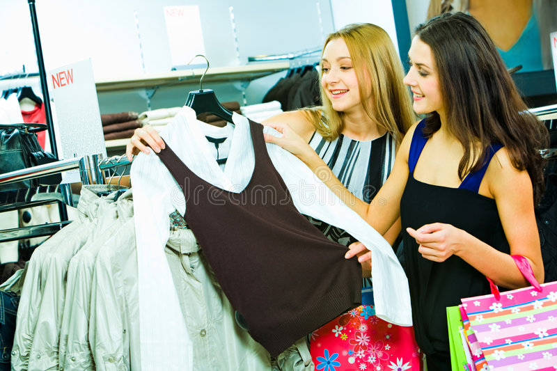 Choosing new clothes. Portrait of two young smiling ladies in the clothes department looking at fashionable shirt during sale stock image