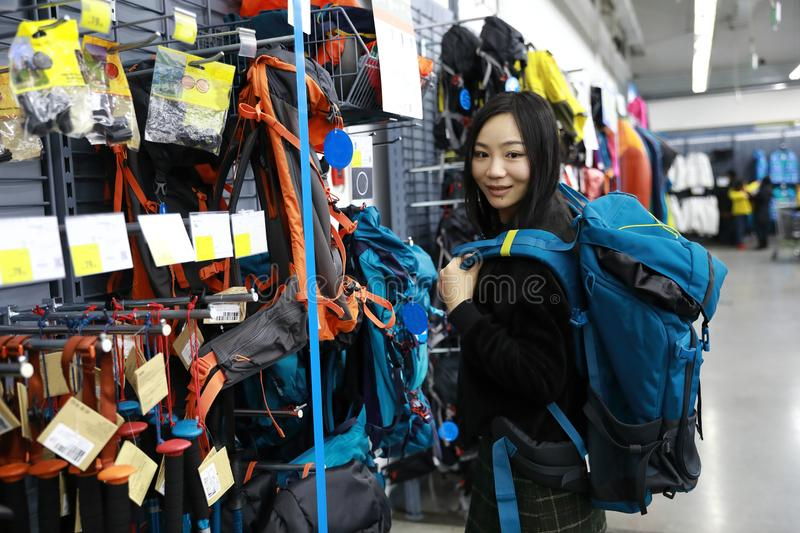 Choosing new knapsack shanghai decathlon shop. Portrait of young smiling lady in the outdoor department looking at fashionable knapsack sale royalty free stock images