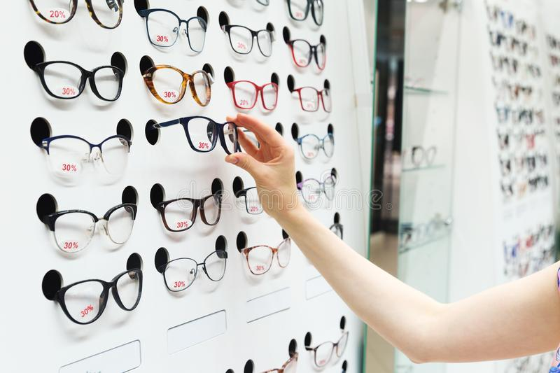 Choosing new optical glasses in optician shop stock photos