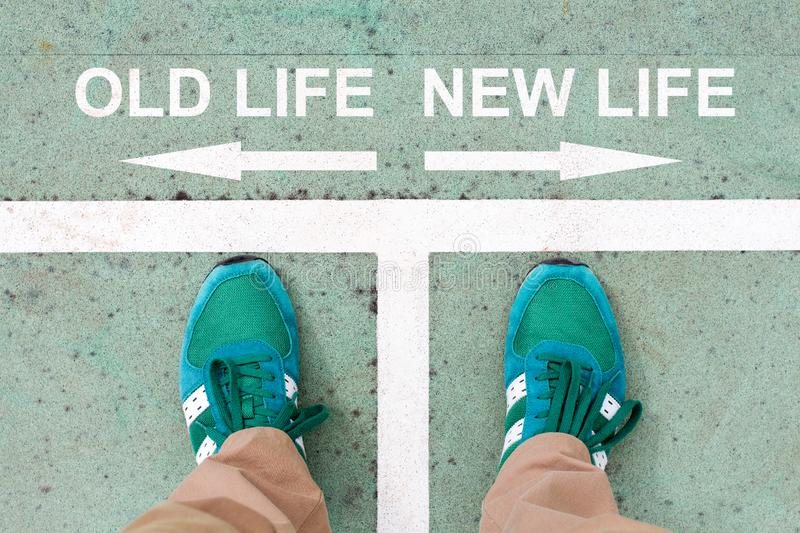 Choosing between old life and new life. Man having to choose between old life and new life and about future symbolized by two feet standing on ground with arrows royalty free stock image