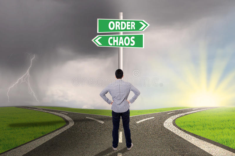 Choosing order or chaos 1. Businessman standing on the road looking at signpost of order and chaos stock images