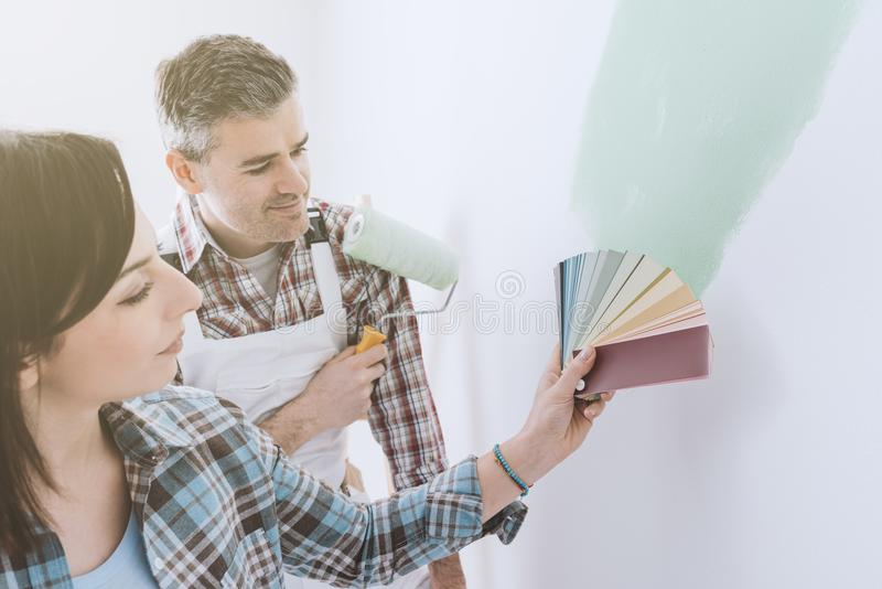 Choosing a paint color. Woman choosing the perfect paint color for her room with a professional painter and decorator, she is holding color swatches stock images