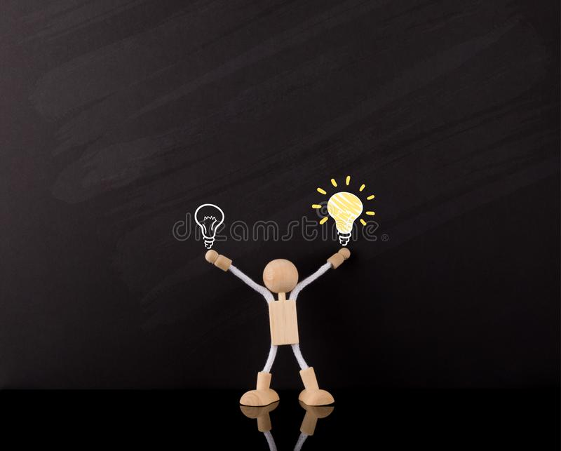 Critical Thinking Skills Concept, Wooden Stick Figure arms up, Big Yellow light bulb sketch, on a chalkboard royalty free stock photos