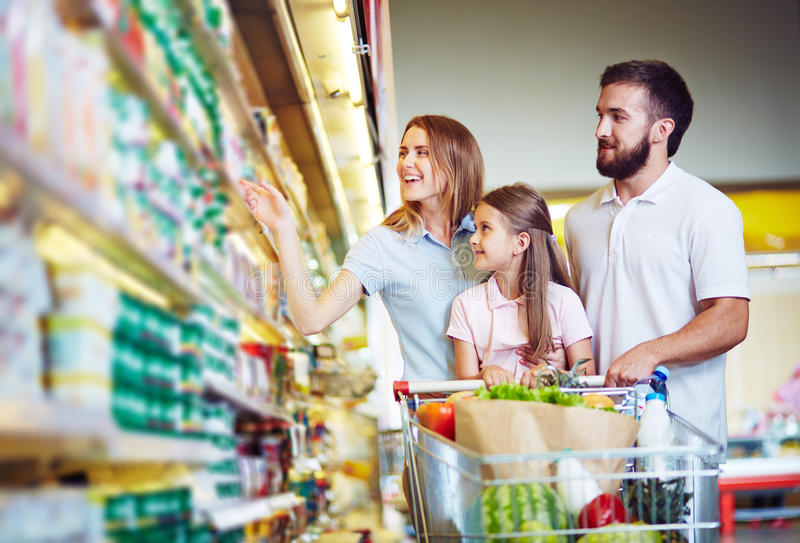 Choosing products in hypermarket. Young family in hypermarket choosing products royalty free stock images