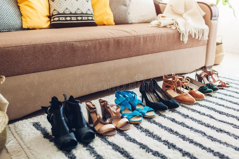 Choosing shoes at home. Hard choice to make from sandals, heels and flats of different styles and color royalty free stock photos