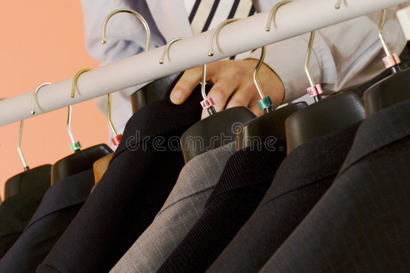 Choosing the suit. The man is chosing the right suit for his working day