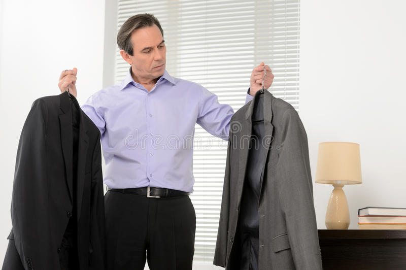 Download Choosing A Suit For Meeting. Mature Businessman Standing With A Stock Image - Image: 32196511