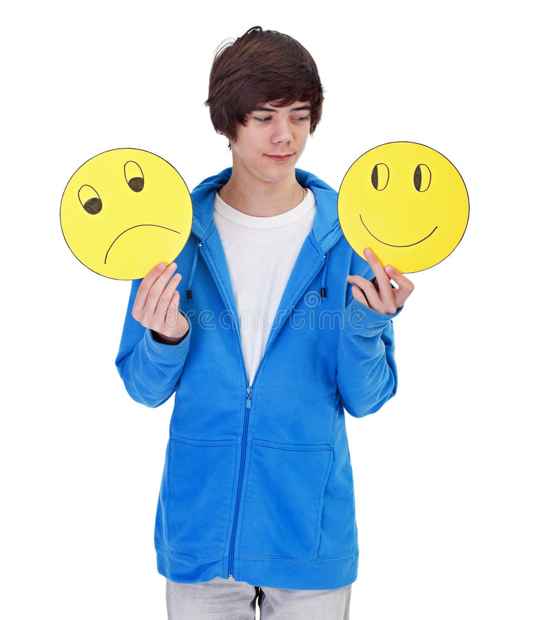 Choosing to be happy. Teenager boy with cheerful and sad masks royalty free stock photo