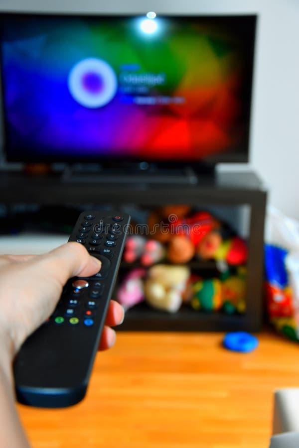 Choosing tv program. Female choosing tv program with remote royalty free stock photos