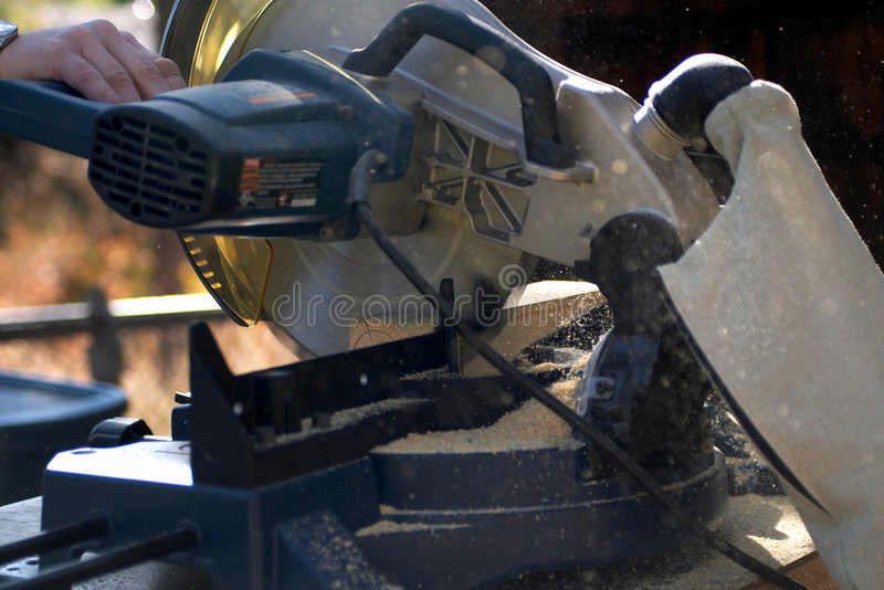 Chop saw. Cutting a piece of lumber with a miter or chop saw stock photo