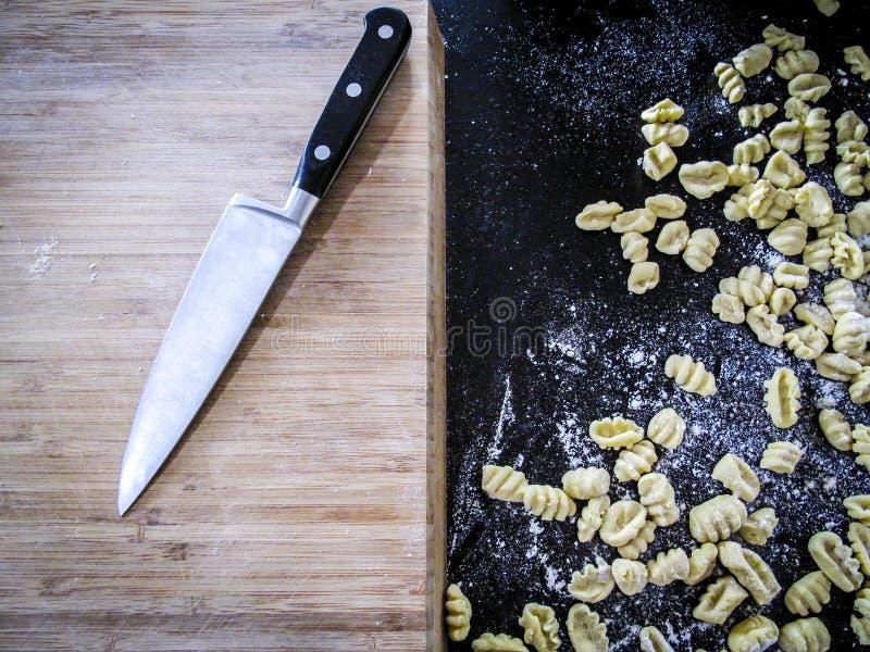 Chopboard und frischer Teigwaren Gnocchi lizenzfreie stockbilder