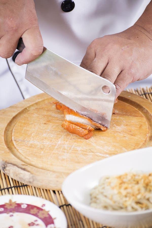 Choping Brathähnchen des Chefs für das Kochen der Nudel stockfotografie