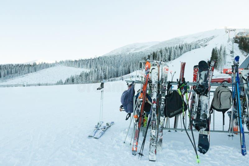 CHOPOK SLOVAKIEN - JANUARI 12, 2017: Skidar, och snowboards som väntar på deras ägare nära apres, skidar stången på sluttande Cho royaltyfri bild