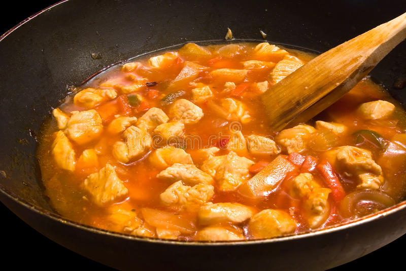 Chopped chicken cooking in a sweet and sour sauce stock image