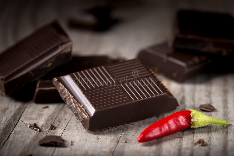 Chopped Chocolate with Red Chilli Pepper. On wooden background closeup. Chunks of Broken dark chocolate bar on wood table macro royalty free stock images