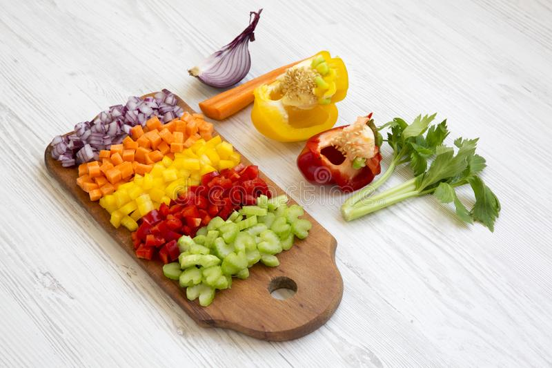 Chopped fresh vegetables arranged on cutting board on white wooden surface, side view. Chopped fresh vegetables carrot, celery, onion, colored peppers arranged stock images
